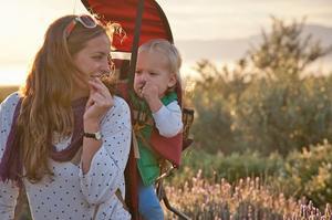 Nina med sonen Noah på ryggen, som alltid under åren i Sydafrika, från det han föddes. På bilden är de två hemma där de bodde i naturreservatet – och luktar på varsin kvist lavendel.