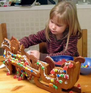Gry Udd garnerar pepparkakshästarna med släde som hon har bakat tillsammans med farmor.