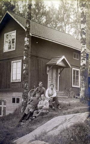 De fyra snickeriarbetarna utanför en byggnad, möjligen snickarverkstaden.