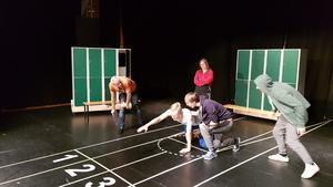 Läraren Erik Nihlgård (i orange) handleder och regisserar föreställningen. Här instruerar han eleverna Ronja Nilsson, Lukas Karlberg och Denis Dalipi i hur de ska mobba Löparen Emil Flygare.