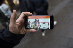 Dilges Akgul visar en bild i sin mobil där en av hans kusiner intervjuas i teve.