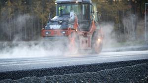 En vägvält plattar till nylagd asfalt.