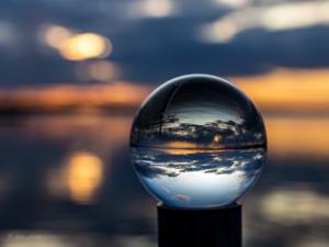 Solnedgång vid Strandbaden i Årsunda reflekterad i kristallkula. Foto: Pia Bergström