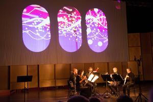 Nordiska Blåsarkvintetten skapar stämningar tillsammans med ögonblickskonst på skärm av Sandra Mozard.