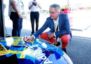 Audis VD Rupert Stadler sätter sin signatur på Mattias Ekströms bil. Foto: Audi Communications Motorsport/Michael Kunkel