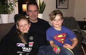 Markus Oscarsson myser med barnen i soffan i villan på Hamre.