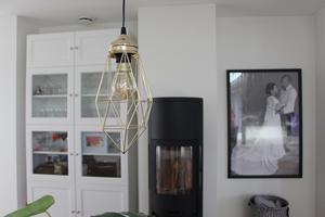 Skir mässinglampa och bröllopsfoto i svartvitt vid kaminen.