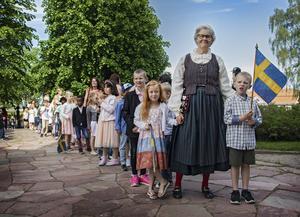 Eleverna på Alftaskolan tågade till kyrkan. Längst fram gick förskoleklassens flaggbärare och fröken.