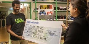 Hanna Hedberg, ordförande i Ladies circle, lämnar över den stora checken till Alamin Nurhussen, platsansvarig på Fritidsbanken.