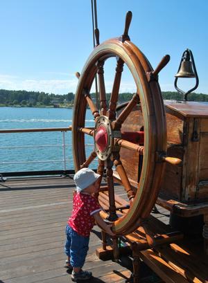 Tvåårige Arvid har visserligen redan viss båtvana - men att styra fyrmastade barken Pommern visade sig vara honom övermäktigt! Men han gjorde ändå ett gott försök under en solig sommardag i Mariehamn, Åland 2011.