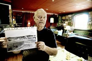 """Förvandlingen. Leif """"Linus"""" Larsson visar två filmer om hur Askersundsverken växte fram och nu har blivit sportbar. Första filmen börjar med den här bilden fråm 1886.Foto: Göran Kempe"""
