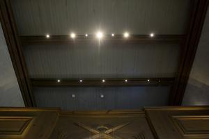 Träbalkarna i taket har lampor som lyser.
