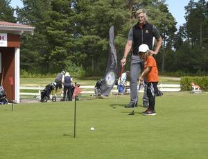 Levi Frost, 6 år, visar golfklubbens nye pro Erik Olsson hur man sänker en lång putt.