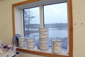 I fönstret står färgburkarna på rad och utanför blänker det från sjön.