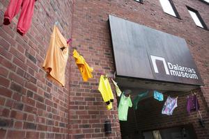 Dalarnas museum har dekorerats med en tvättlina där hänger kläder i regnbågens färger.