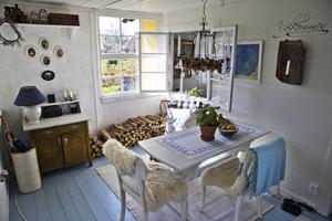 I det första rum man kommer in i har Anna gjort iordning ett mysigt matrum med levande ljus ovanför bordet. Nästa rum är vardagsrummet med kamin och blommiga överdrag på stolarna.