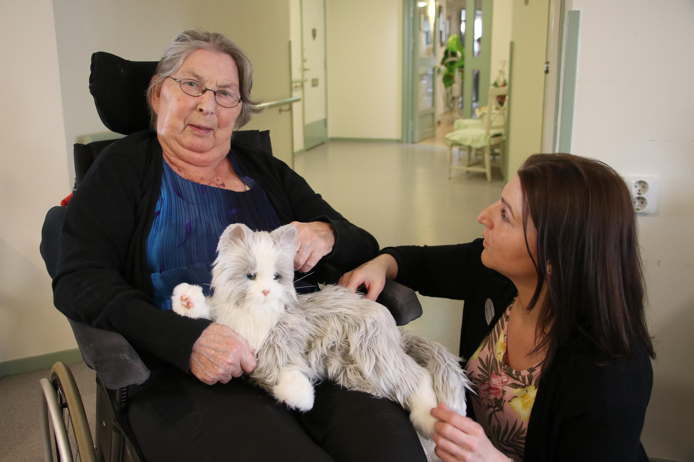 Ingrid Karlsson har tidigare haft katt och tycker det är mysigt att få låna med sig robotkatten in på rummet. Enhetschefen Linda Viberg har sett vilken betydelse katten har fått.