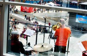 """Skön jazz i solen. Det svängde ordentligt när en kvintett av länets mest välrenommerade jazzmusiker i går serverade örongodis från Länsförsäkringars terrass. Mattias Nordqvist, piano, Roy Okutani, trumpet, Waldemar Swiergiel, trombon, Dan Svedberg, bas samt Erik Edlund, trummor, verkade njuta av stunden lika mycket som åhörarna på det soldränkta torget. """"En fantastisk scen, så användbar"""", sa flera röster i vimlet om terrassen och det spekulerades friskt om huruvida det är där presidenten kommer att uppenbara sig  i kväll.  Foto: Lars-Eje Lyrefelt"""