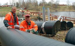Per Hellestig och Stig Gustavsson vid några av de  42 ubåtsliknande pontoner som bron försågs med 2009 för att öka flytkraften och höja träkonstruktionen över vattenytan.