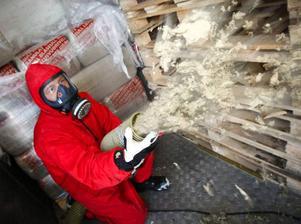 Iklädd mask och skyddskläder sprutar Peter Emanuelsson isolering.  En normal vind tar omkring en timme att fylla.Foto: Olof Sjödin