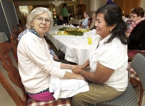 Inga-Lill Severin och Supranee Phadontree firar internationella beröringsdagen med handmassage.