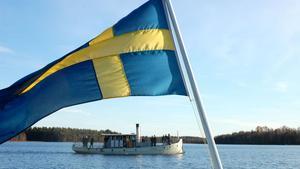 Ångbåten Laxen ute på Saxviken i Mora. I förgrunden båten Eriks flagga.
