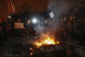 Demonstranter med plakat och flaggor runt en brinnande tidningslåda i Washington.