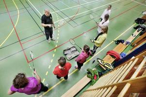 Gunnar Haggelin visar för gruppen hur en racket ska hållas.– Kom ihåg till nästa gång, lång serve och clear, säger han.