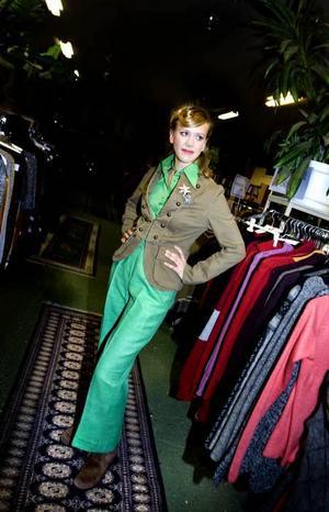 En ledigare klädsen i ärtgröna byxor med matchande skjorta. Till det en militärinspirerad kavaj med mässingknappar och två broscher. Fyndat på Biståndsgruppen.