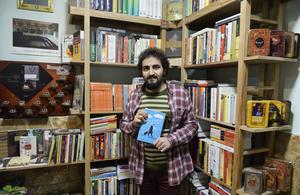 Majid Garousi plockar med böckerna i den välfyllda bokaffären i centrala Teheran.