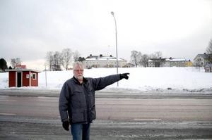 Berndt Norrman står vid E45:an och pekar mot den telestation som han vill få fast bredband ifrån, ett stenkast åt andra hållet ligger hans hem.