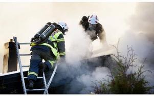 Brandmän tar hål i taket för att ventilera ut all den rök som fyllt villan. Foto: Peter Ohlsson/DT