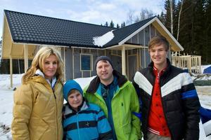 Bo och Annechristine Schöllin ser uppförandet av fritidshus som ett familjeprojekt. Här står Annechristine Alexander, Bo och Hampus framför det första huset som byggs.