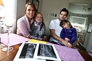 På utsidan syns och märks ingenting, men sexåriga Saga Wallberg som här sitter i mamma Marias knä har nyligen fått ett titanstag inopererat i ryggen. Ett ingrepp som har varit omvälvande för hela familjen. På bilden även pappa Daniel med syster Alva i sitt knä.