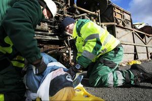En av de skadade dras ut genom hjulhuset på bussen.
