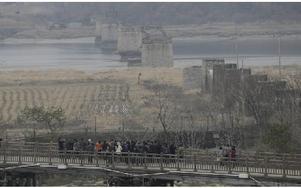Turister tittar norrut mot Nordkorea och Frihetsbron, som förstördes under Koreakriget, nära gränsbyn Panmunjom på fredagen.
