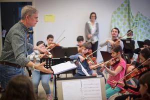 Dirigerar. Musikpedagogen Per Lundström hjälper till när Ron Davis Alvarez greppar fiolen och sätter sig med barnen.