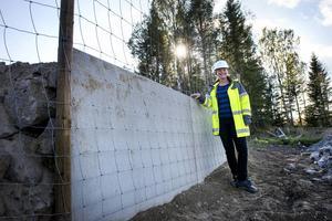 En hög mur på skogssidan av viltstaketet.