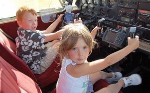 Isabell och Vilgot Nilsson är inte riktigt gamla nog att  köra en Piper Cherokee 180, men det stoppar dem inte från att förklara hur man åker upp och ned. Foto: Stefan Rämgård