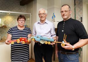Laila Grubb, ordförande i Selångers hembygdsförening, Stig Jansson och Per Jansson, barn och barnbarn till leksakstillverkaren Evert Jansson håller i några av hans alster.