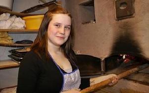 Lisa Andersson prövar på att grädda en tunnbrödskaka i den vedeldade ugnen.Foto: BIRGIT NILSES GRÖNDAHL
