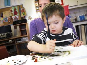 KONCENTRATION. Treåriga Linus Lundsten satt djupt koncentrerad i mamma Anna Mattssons knä.