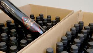 Wolfs medlemmar har handsignerat varje flaska med pennor för glas och keramik. Henrik Larsson har sedan använt en varmluftspistol för att värma fast autograferna.