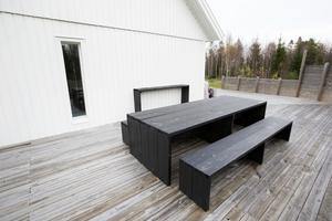 Det svarta träbordet på altanen har plats för många.