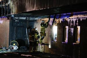 Brandmän förde undan bränt virke för att undersöka takkonstruktionen.