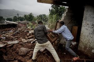 Två män kämpar i lermassorna i den del av landet där bland annat FN-föreningen i Örnsköldsvik har stöttat i många år. Bild: AP