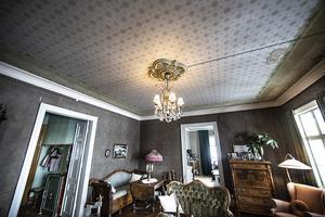 Taket i salen är en tapet. De tror att under eller över tapeten är det pärlspånt. Väggen har fortfarande den tapet som sattes upp första gången för över 100 år sedan.