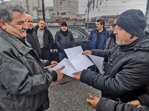 Taxichaufförerna Mohamad Ali Anayati och Ara Khizry samlar ihop papperna för namninsamlingen.