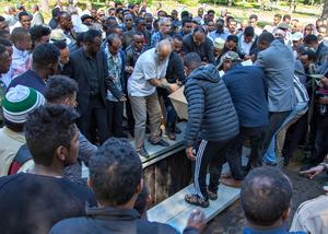 Flera personer hjälps åt att sänka ner kistan.