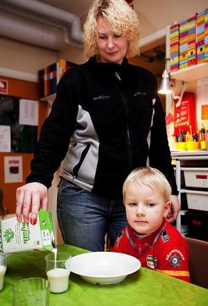 Maria Bergqvist häller upp mellanmjölk till sonen Axel.